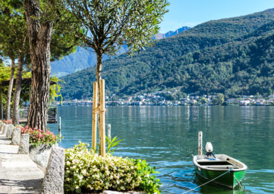 Vacation summer sunny lake view. Lonely wooden green boat on serene Lugano lake surrounded by hills, green trees, flowers blossoms and clear blue sky in Morcote, Switzerland