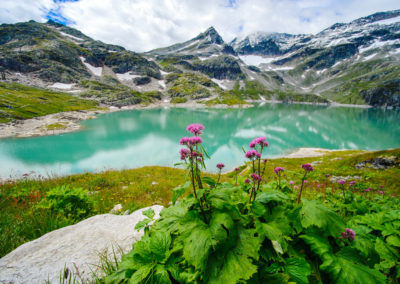 alps landscape - glacial lake in front of mountains and blue sky