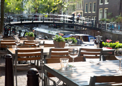 Amsterdam restaurant cafe tables set for outdoor dining with glassware and view of canal bridge in the background