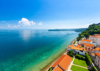 Aerial panorama view of Piran city, Slovenia. Look from tower in church. In foreground are small houses, Adriatic sea in background. Summer weather in famous tourist destination