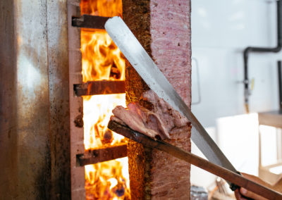 Turkish Doner Kebab, Shawarma or Gyros. Chef cutting with doner knife Traditional Turkish Doner Kebab meat, shawarma or gyros. Turkish, greek or middle eastern arab style doner kebab food spit.