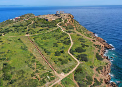 Aerial drone bird's eye view of archaeological site of Cape Sounio and magnificent Ancient temple of Poseidon on top of deep blue bay, South Attica, Greece