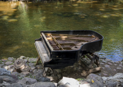abandoned gran piano, rundown piano by a river bank (Vilnia river) in Uzupis artists quarter in Vilnius, Lithuania, bohemian atmosphere. Republic of Uzupis