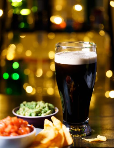 Glass of stout with nachos, tomato salsa and guacamole. Bar bottles in bokeh, high resolution