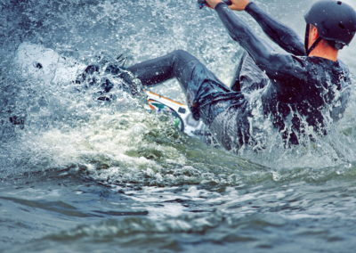 Active man riding on the wakeboard holding a rope having healthy summertime on the river on the background of sky and trees