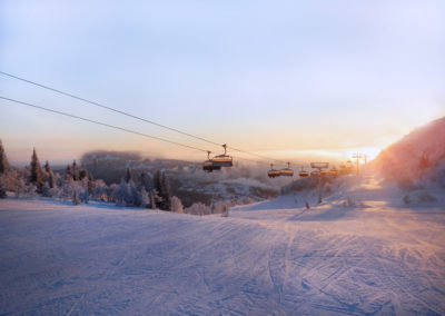 Ski slope and cable car at sunrise.